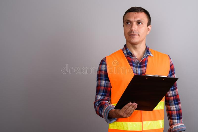 Man construction worker holding clipboard against gray backgroun stock photography