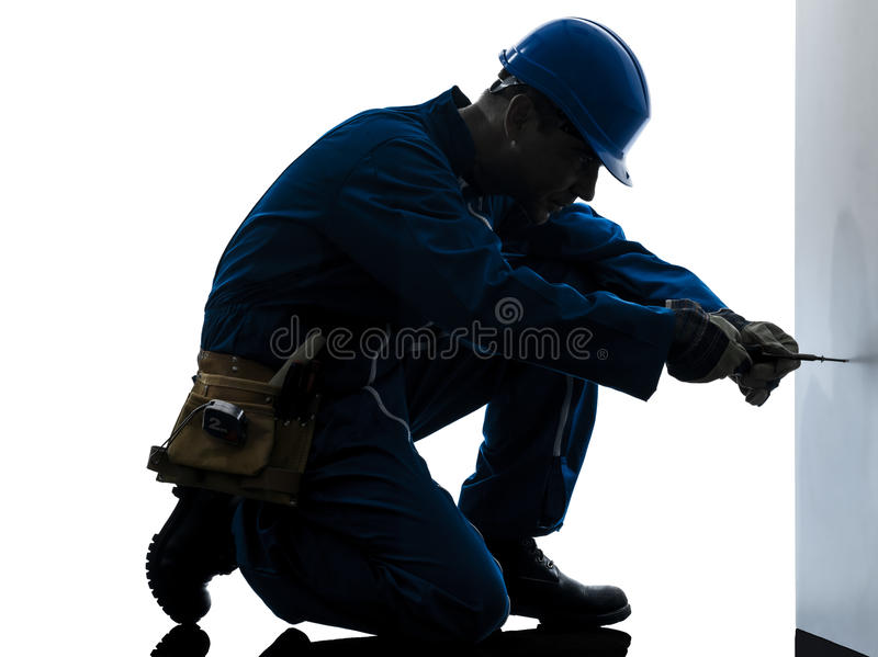 Man construction worker screwdriving silhouette. One caucasian man construction worker screwdriving silhouette in studio on white background stock photography