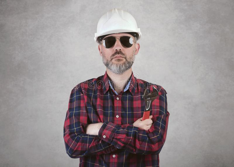 Man construction worker with a white helmet and sunglasses holding a wrench royalty free stock photography