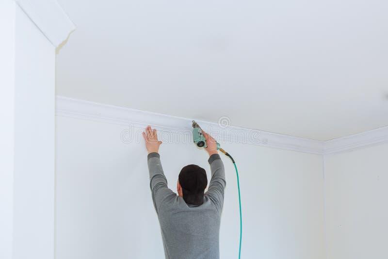 Man constructor renovates room interior with a plastic molding. Man constructor renovates room interior with a wood crown molding in the ceiling stock photos