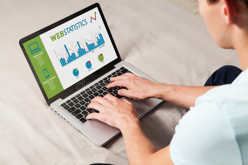 Man consulting web statistics in a laptop computer at home. stock image