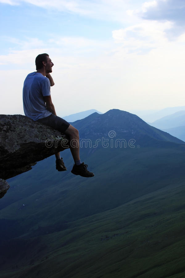 Man contemplating on top of a rock stock images