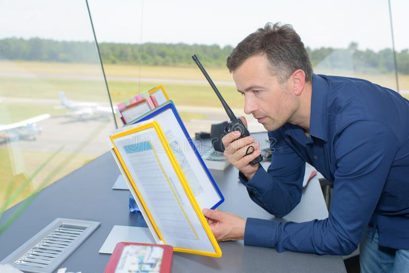 Man in control tower talking into two way radio. Control stock photography