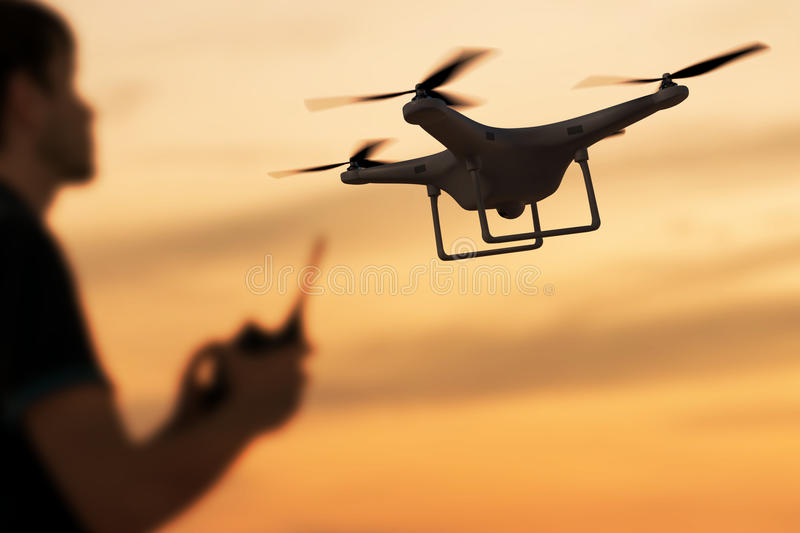 Man is controlling flying drone at sunset. 3D rendered illustration of drone.  royalty free stock image