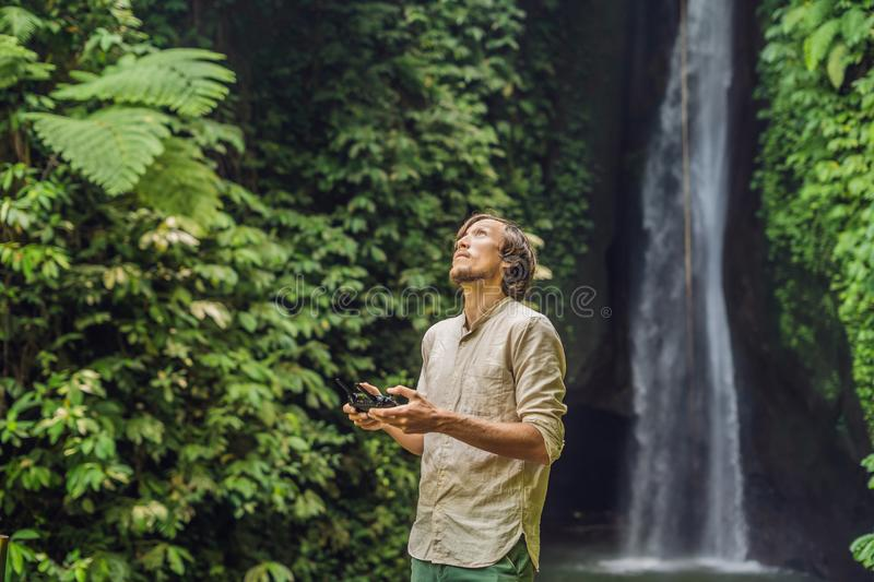 The man controls the drone against the background of the forest and the waterfall royalty free stock photos