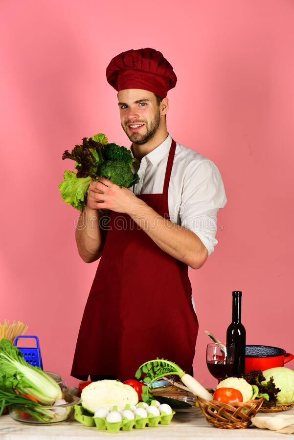 Man in cook uniform offers salad. Chef with smiling face stock photography
