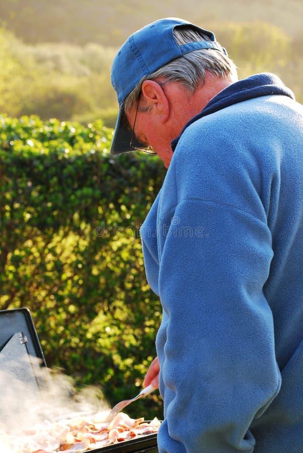 Older Man Enjoying Cooking Outdoors royalty free stock images
