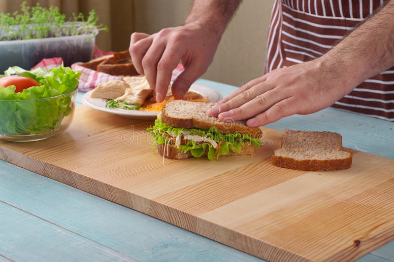 Man cooking big sandwich with chicken stock images
