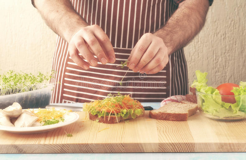 Man cooking chicken sandwich royalty free stock photo