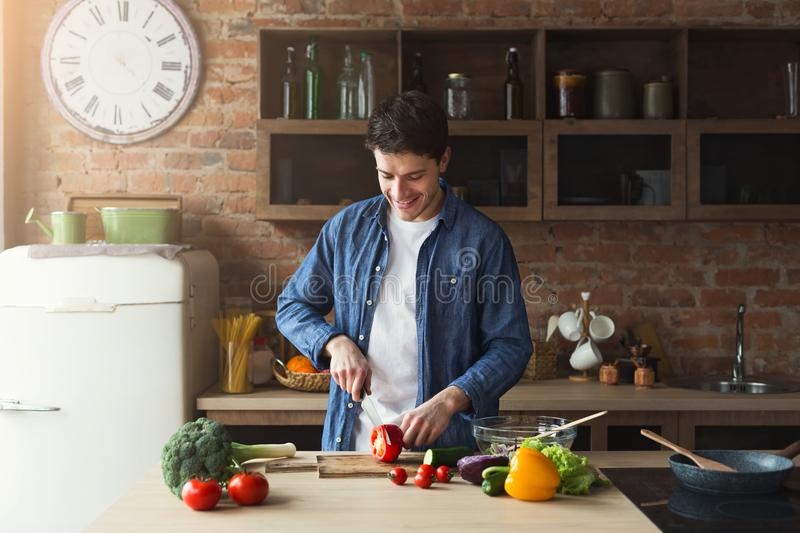 Man preparing delicious and healthy food in the home kitchen. Man cooking delicious and healthy food in the loft kitchen at home on sunny day. Preparing royalty free stock photography