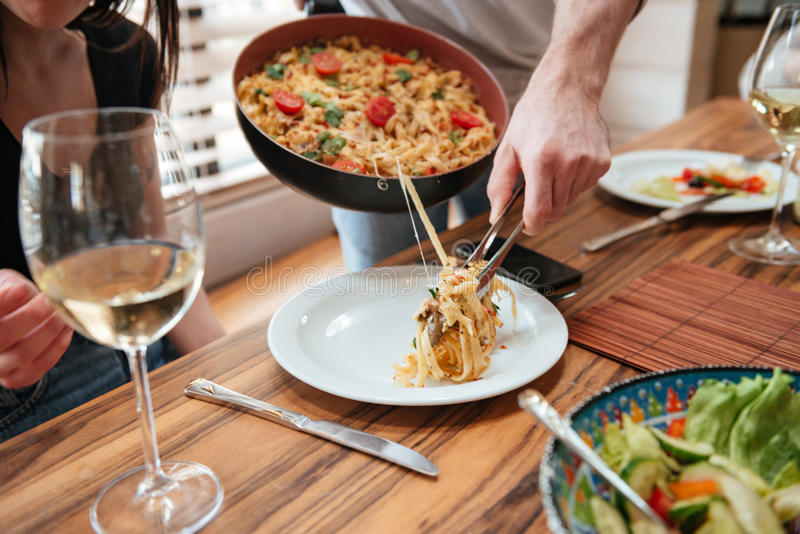 Man cooking dinner and putting food into the plate royalty free stock photo
