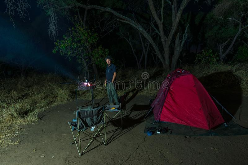 Man cooking with fire wood and braai equipment by night. Tent and chairs in the foreground. Adventures in african national parks. Man cooking with fire wood and stock image