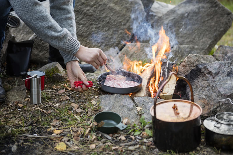 Man Cooking Food Over Bonfire At Campsite. Cropped image of man cooking food over bonfire at campsite stock photo