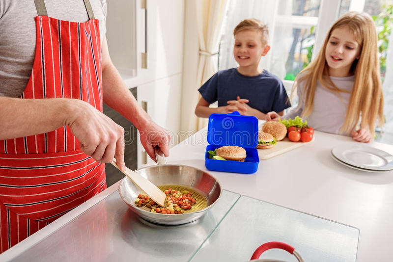Man cooking healthy food for his family. Hungry children are waiting for breakfast at home. They are sitting at table and smiling. Focus on father hands frying royalty free stock photography