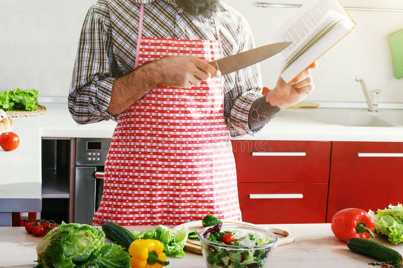 Man cooking making vegetable salad and reading recipe book. Man cooking at kitchen making healthy vegetable salad and reading recipe book stock images