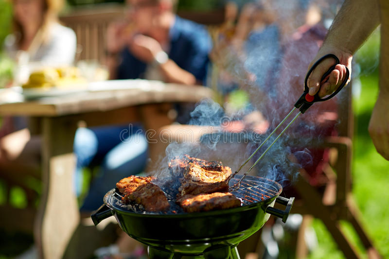 Man cooking meat on barbecue grill at summer party stock image