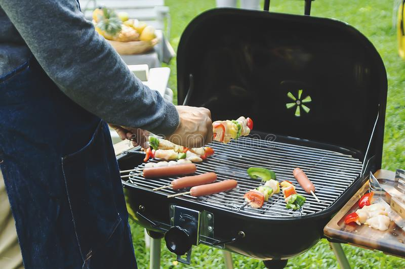 Man cooking meat on barbecue for summer family dinner in the backyard of the house royalty free stock photos