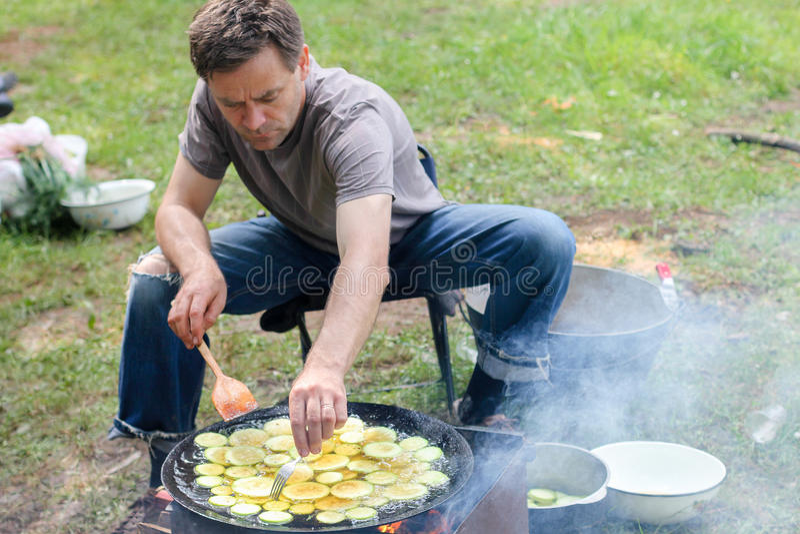 Man Cooking Meat Over Bonfire At Campsite. Carpathians stock images