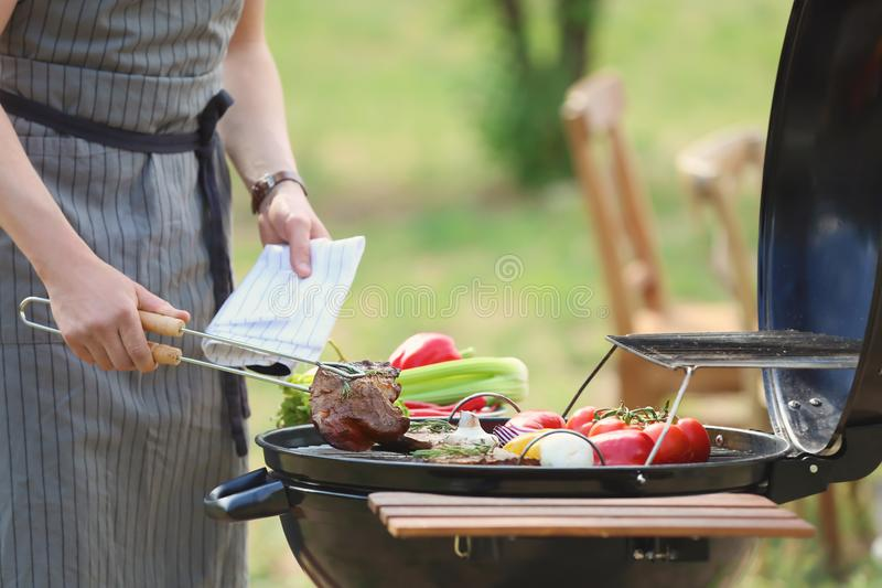 Man cooking meat and vegetables on barbecue grill outdoors. Young man cooking meat and vegetables on barbecue grill outdoors stock photography