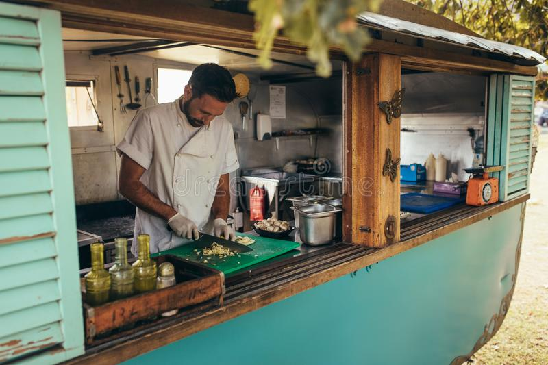 Man cooking in a mobile food truck royalty free stock images