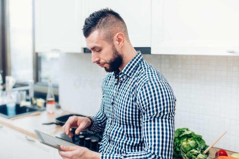 Man cooking in new kitchen, using tablet for recipes and looking on internet stock image