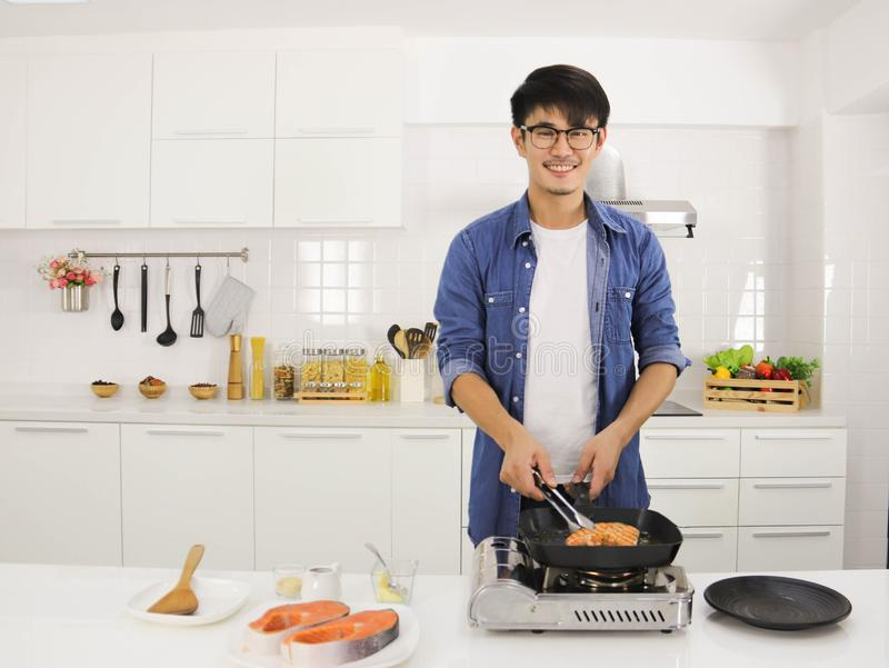 A man cooking salmon steak in the kitchen. Young handsome man wearing eye glasses standing in the kitchen cooking salmon steak in the pan with a plate of salmon stock images