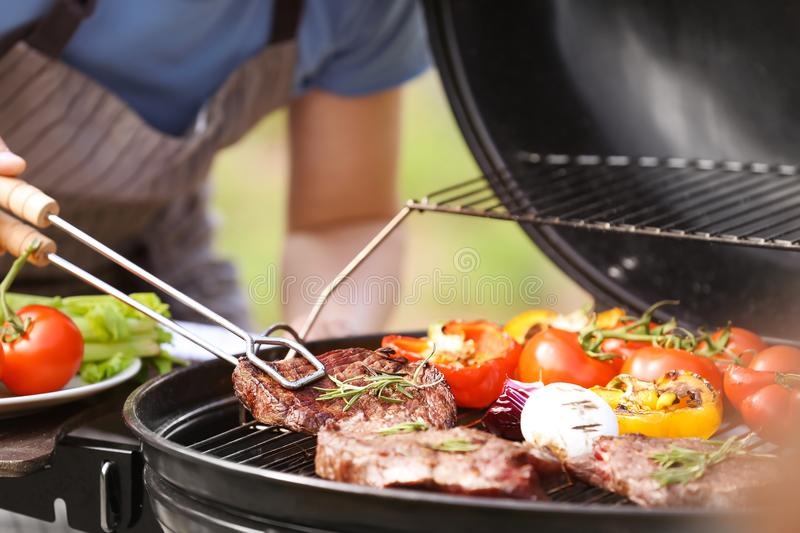 Man cooking tasty meat and vegetables on barbecue grill outdoors. Man cooking meat and vegetables on barbecue grill outdoors royalty free stock image