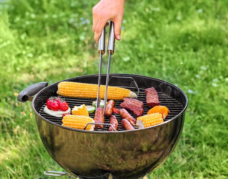 Man cooking tasty vegetables, sausages and meat on barbecue grill outdoors royalty free stock photos
