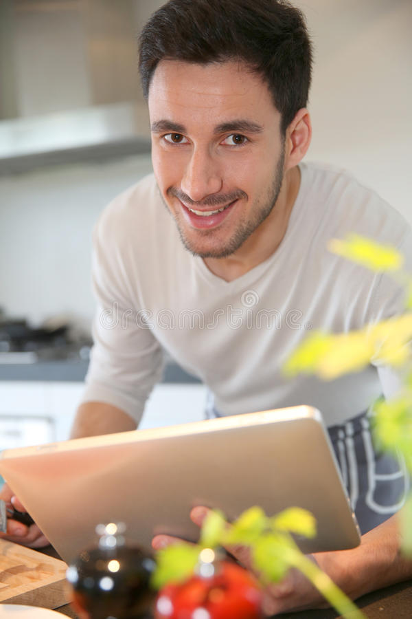 Man cooking and using tablet. Man in domestic kitchen looking at recipe on tablet stock photo
