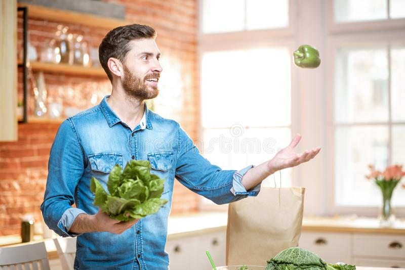 Man cooking vegan meals on the kitchen. Handsome man throwing up green pepper while cooking vegan meals on the kitchen at home stock photography