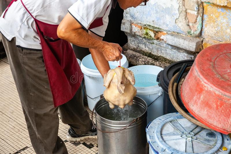 Man cooks chicken on the street of Ipoh royalty free stock image