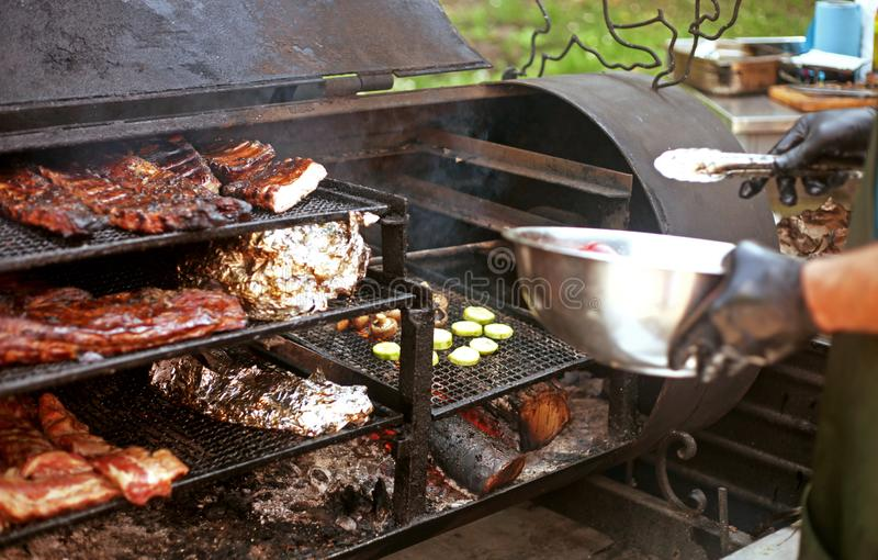 Man cooks different kinds of meat and vegetables on the grill outdoors stock photos