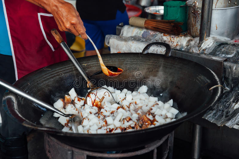 Man cooks at Kimberly Street Food Night Market. Man is cooking at Kimberly Street Food Night Market in George Town, Malaysia stock image
