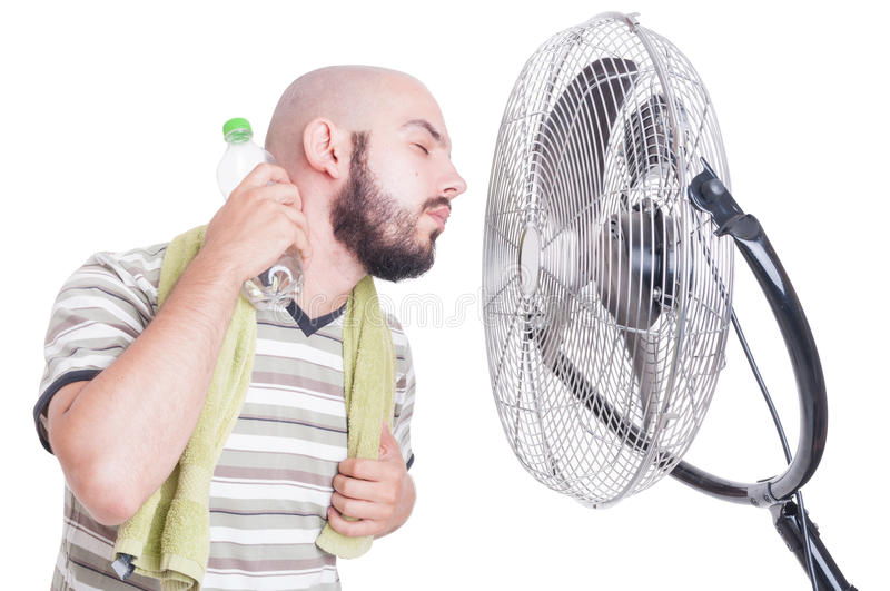 Man cooling his neck with cold water bottle and fan stock images