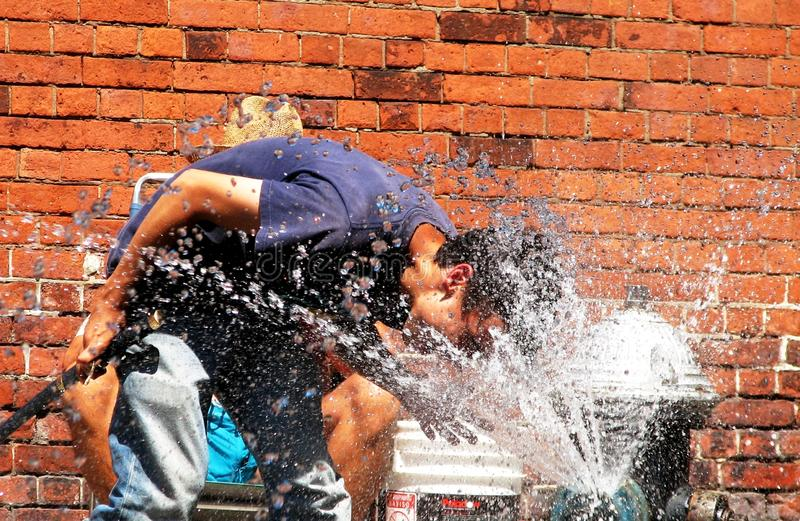 A man cools off from the Manhattan heat by bathing with a fire hydrant - NYC. A fire hydrant, also called a fireplug, fire pump, jockey pump, or simply pump, is royalty free stock photo