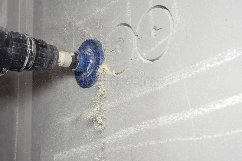 Man with cordless hand drill drilling a hole in concrete royalty free stock photo