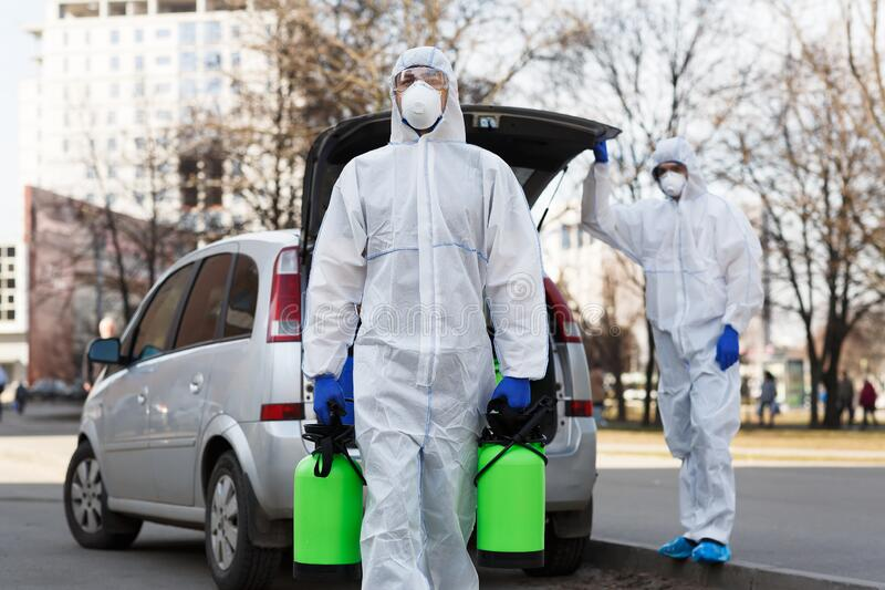 Man in coronavirus hazmat suit carrying disinfection gas. Or spray for struggle with covid-19, copy space stock photos