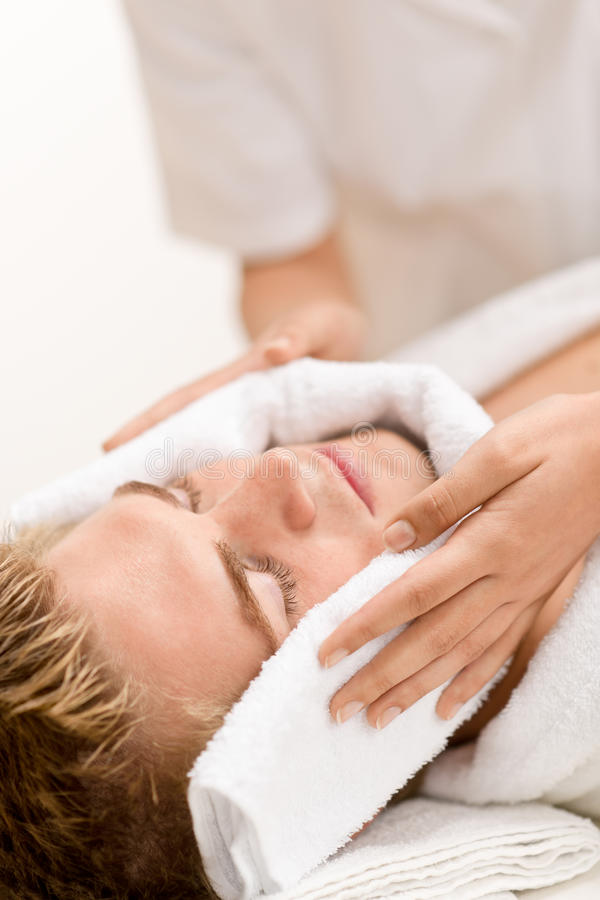 Man cosmetics - luxury spa treatment. Receiving facial massage stock images
