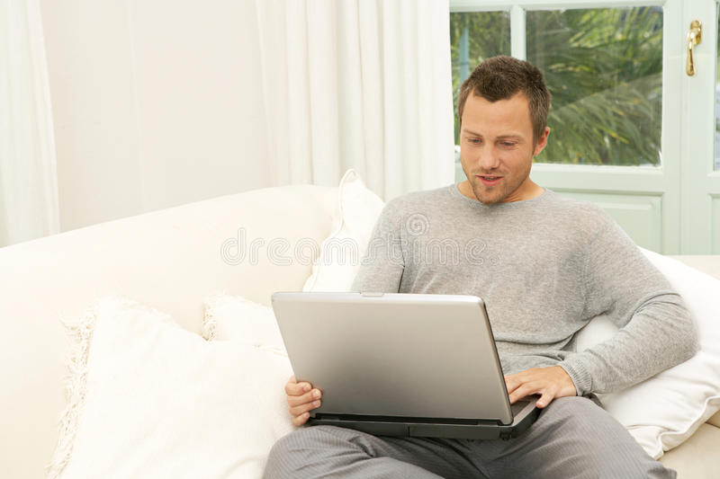 Download Man On Couch With Laptop At Home. Stock Photos - Image: 29314673