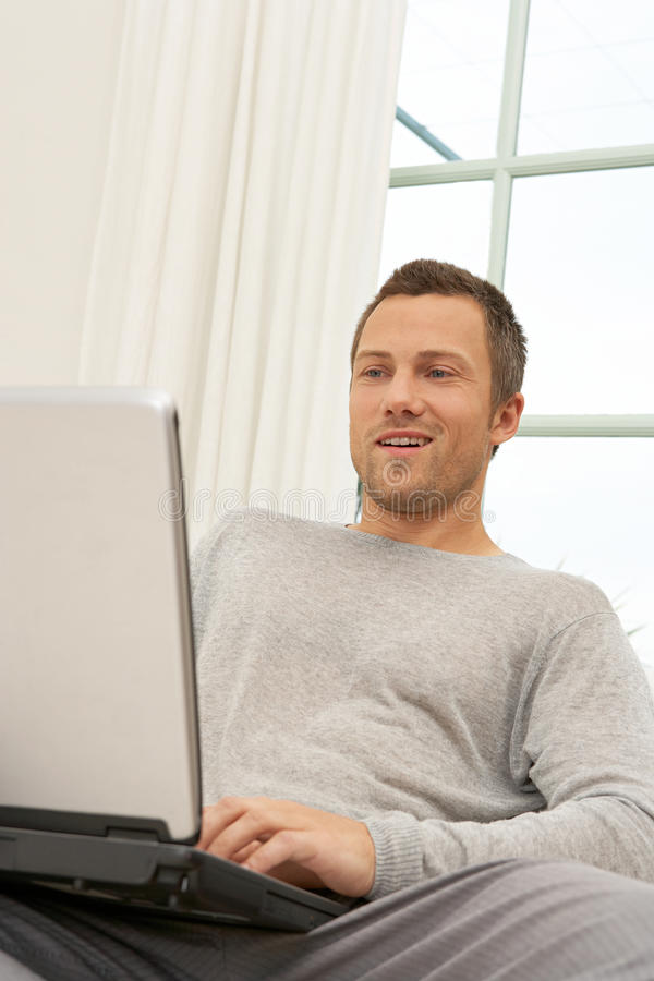 Man On Couch With Laptop At Home. Stock Image