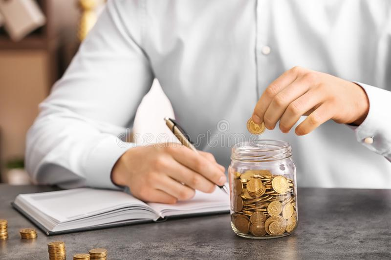 Man counting coins at table. Savings concept royalty free stock image