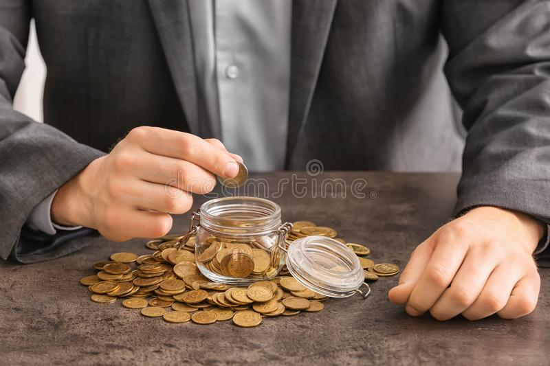 Man counting coins at table. Savings concept stock images