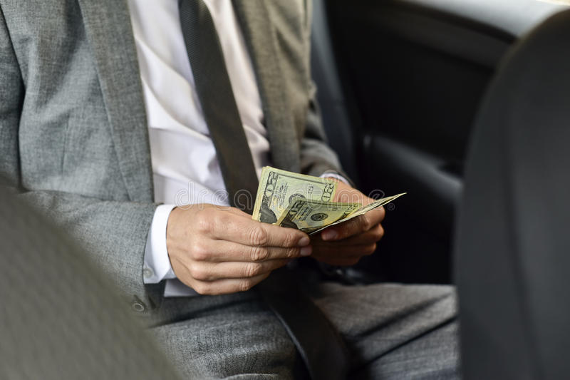Man counting dollar bills stock image