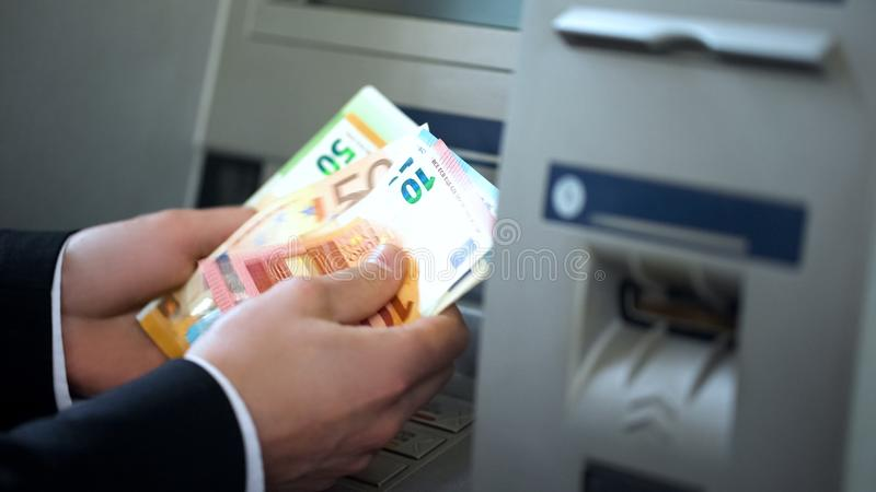 Man counting euros withdrawn from ATM, 24h service, easy banking operation royalty free stock photography