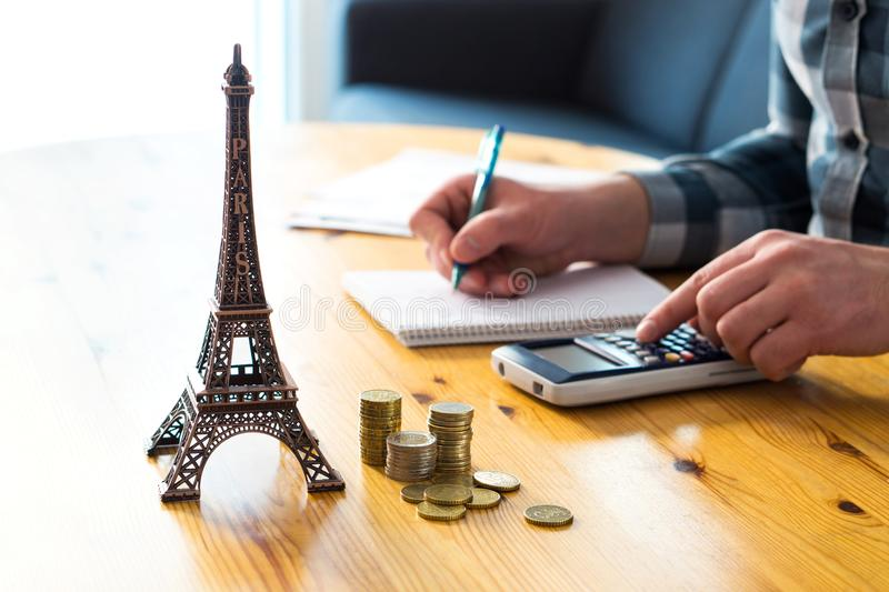 Man counting travel budget, vacation expenses or insurance cost. Traveler planning holiday in Europe. Cheap flights and hotel. Money and little Eiffel Tower stock images
