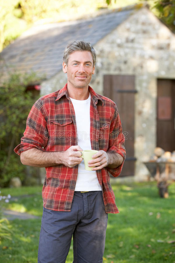 Man in country garden. Having a drink royalty free stock images
