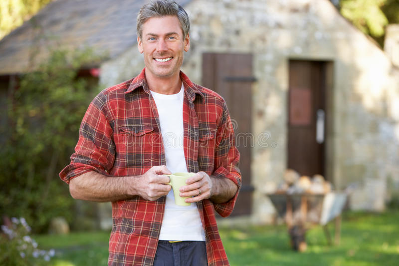 Man in country garden. Holding a cup stock images