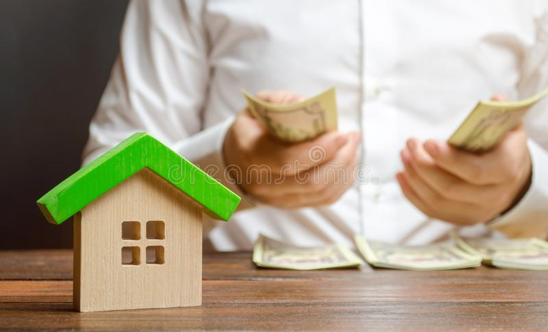 A man counts money on the background of the figures of the house. Calculation of property tax, payment of utilities. Counting royalty free stock photo