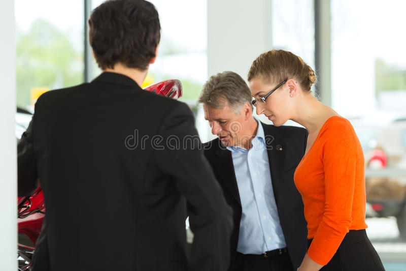 Man With Couple  Looking Beneath A Hood Stock Images