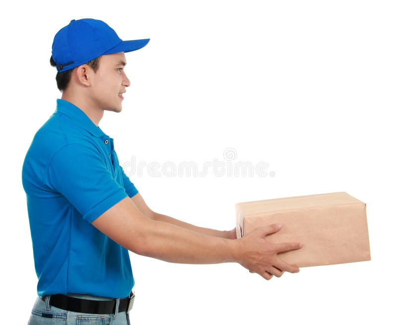 Man courier in blue uniform. Young man courier in blue uniform streching out his hand to give the packages stock images